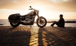 Man sitting next to motorcycle wwatching the sunset