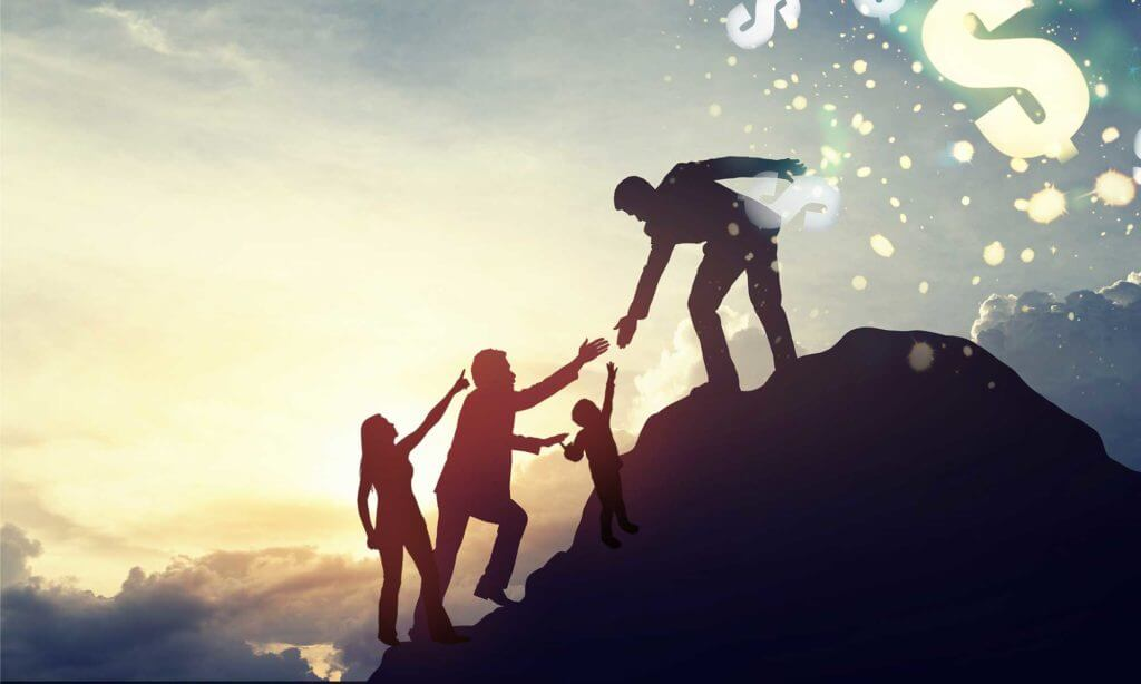 Silhouette of man helping a family to the top of a hill