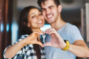 Young couple holding a house key while making a heart with their hands